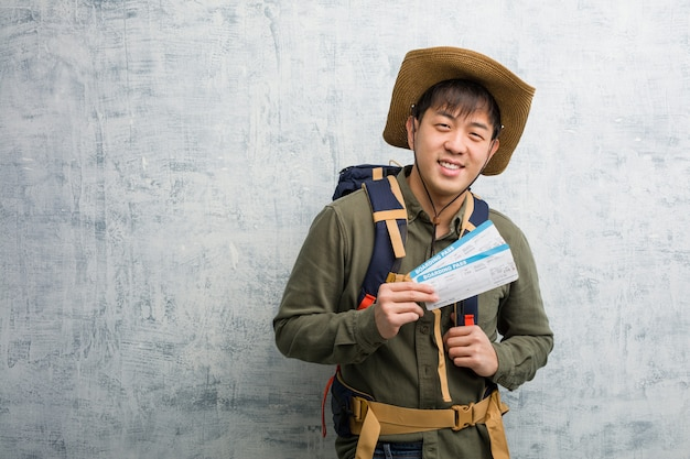 Il giovane uomo cinese dell'esploratore che tiene i biglietti di aria allegri con un grande sorriso Foto Premium