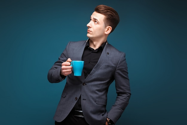 Il giovane uomo d'affari attraente in rivestimento grigio e camicia nera tiene la tazza blu Foto Premium