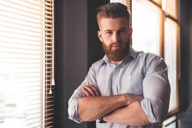 Il giovane uomo d'affari barbuto bello sta esaminando la macchina fotografica. Foto Premium