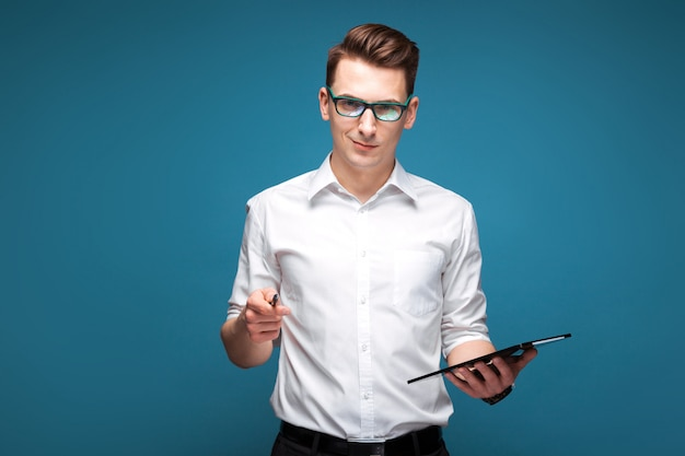 Il giovane uomo d'affari bello in orologio costoso, i vetri neri e la camicia bianca tengono la compressa e la penna Foto Premium
