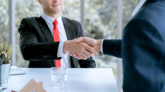 Il giovane uomo d'affari e il cliente acquirente domestico avevano raggiunto insieme i mezzi target e avevano firmato il contratto di vendita. Foto Premium