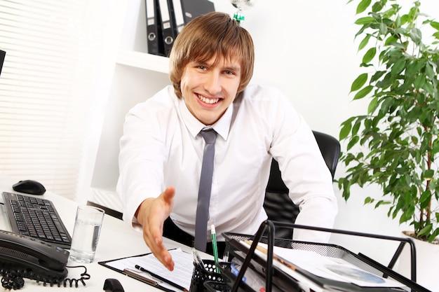 Il giovane uomo d'affari ti dà il benvenuto Foto Gratuite