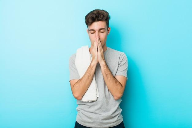 Il giovane uomo dell'adolescente di forma fisica che si tiene per mano dentro prega vicino alla bocca, si sente sicuro. Foto Premium