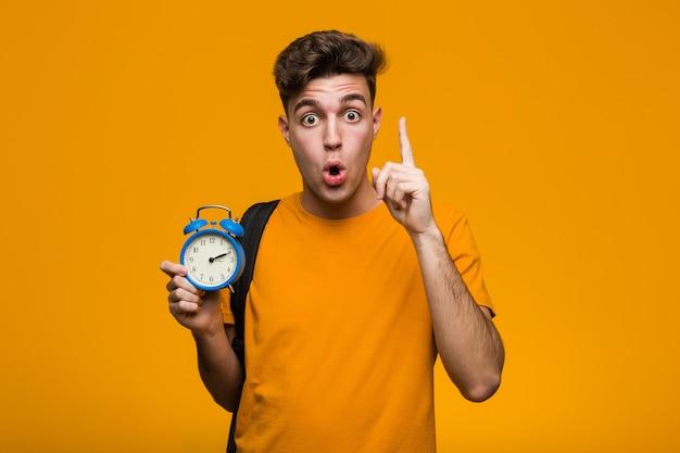 Il giovane uomo dello studente che tiene una sveglia si è disteso pensando a qualcosa che esamina uno spazio della copia. Foto Premium