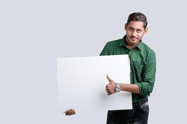 Il giovane uomo indiano che mostra lo spazio in bianco canta il bordo sopra fondo bianco Foto Premium