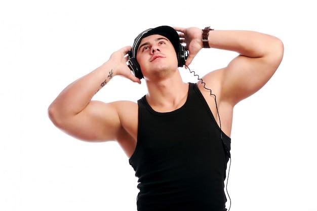 Il giovane uomo muscoloso ascolta musica Foto Gratuite