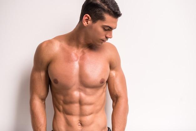 Il giovane uomo muscoloso è in piedi Foto Premium