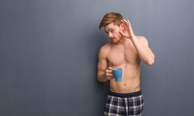 Il giovane uomo senza camicia di rosso prova ad ascoltare un gossip. ha in mano una tazza di caffè. Foto Premium