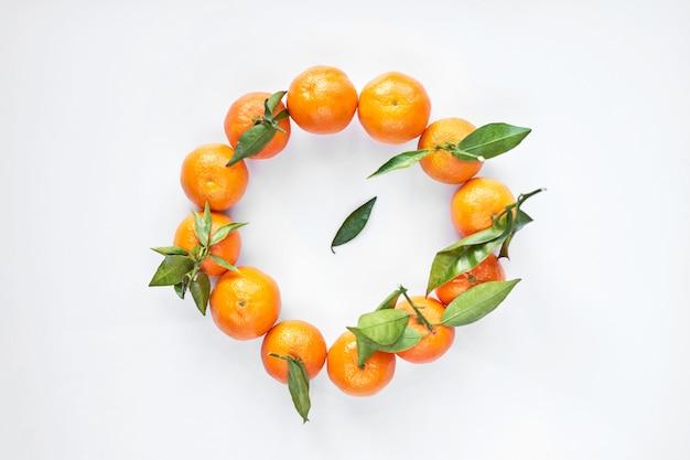 Il giro dei mandarini o dei mandarini freschi arancio con le foglie verdi si trova su un fondo bianco. vista dall'alto. Foto Premium