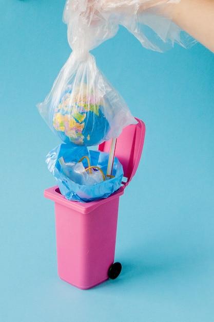 Il globo terrestre si trova nella spazzatura. il globo si trova in un mucchio di plastica. inquinamento plastico della natura Foto Premium