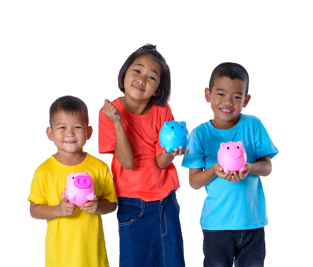 Il gruppo di bambini asiatici si diverte con il porcellino salvadanaio isolato su bianco Foto Premium