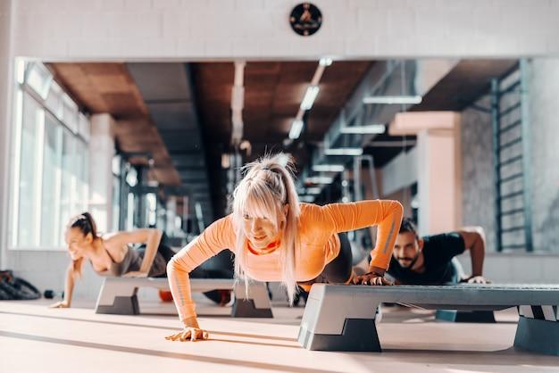 Il gruppo di gente che sportiva fare push up su stepper in palestra. messa a fuoco selettiva sulla donna bionda, in specchio di sfondo. Foto Premium