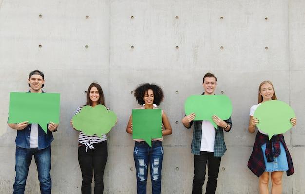 Il gruppo di giovani adulti all'aperto che tengono il copyspace vuoto del cartello ha pensato le bolle Foto Premium