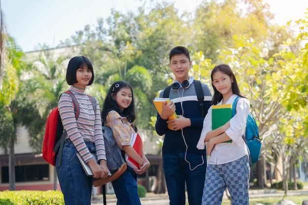 Il gruppo di giovani felici dello studente che cammina all'aperto, diversi giovani studenti prenota all'aperto concetto Foto Premium