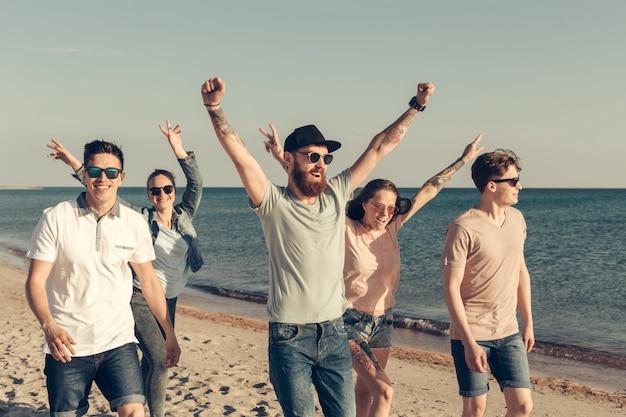 Il gruppo di giovani gode della festa estiva alla spiaggia Foto Premium