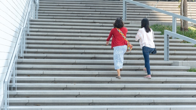 Il gruppo di persone sul retro sta camminando sul paesaggio di scala di cemento esterno. Foto Premium