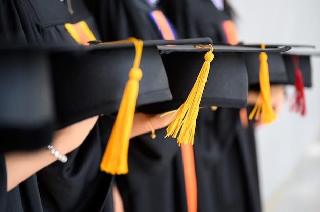 Il gruppo di studenti laureati portava un cappello nero, cappello nero, alla cerimonia di laurea all'università. Foto Premium