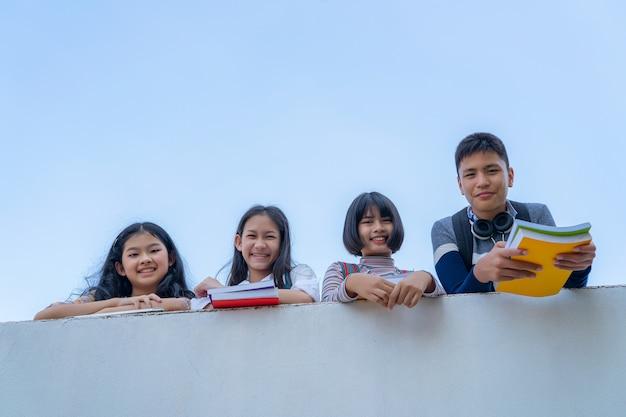 Il gruppo di studenti ride la condizione felice insieme sopra il cielo del bule del balckground del passaggio pedonale della parete Foto Premium