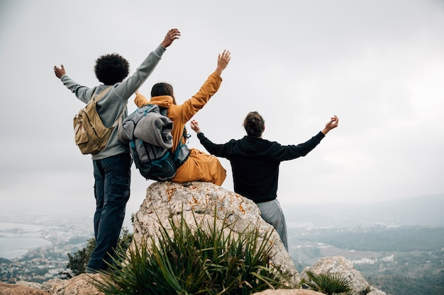 Il gruppo di viandanti che si siedono sopra la montagna alzano fuori allungando le loro mani Foto Gratuite