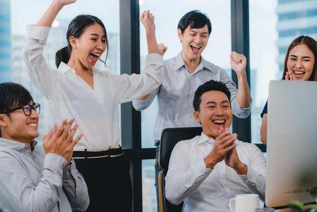 Il gruppo millenario di giovani persone di affari dell'asia l'uomo d'affari e la donna di affari celebra dare cinque dopo avere trattato la sensibilità felice e la firma del contratto o dell'accordo nella sala riunioni in piccolo ufficio moderno. Foto Gratuite