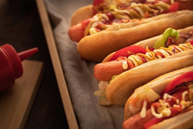 Il hot dog con pepe, il pomodoro, la lattuga e l'insalata si mescolano su di legno. Foto Premium