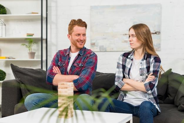 Il jenga di legno davanti alle giovani coppie con il braccio ha attraversato l'esame l'un l'altro Foto Gratuite