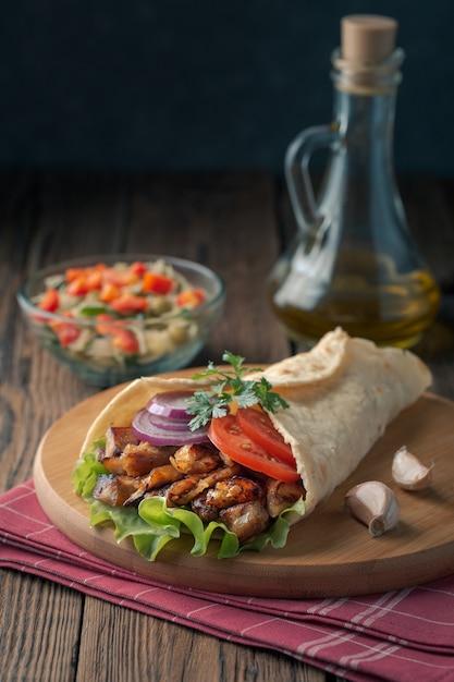 Il kebab di doner giace sul tagliere. shawarma con carne di pollo, cipolle, insalata si trova su un vecchio tavolo di legno scuro. Foto Premium