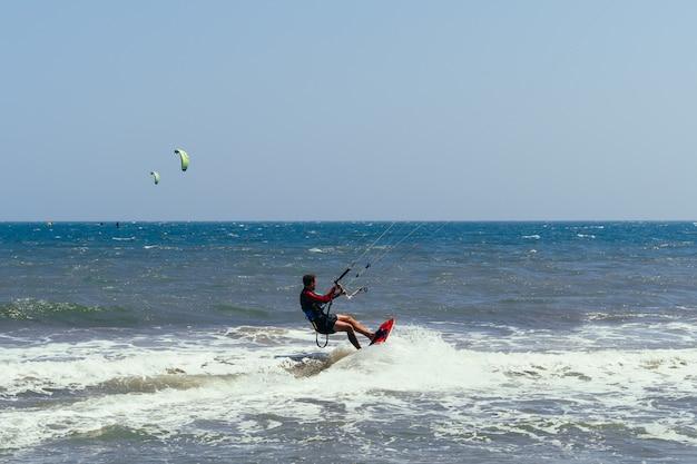 Il kitesurfer maschio si muove sulla scacchiera sulle onde del mare Foto Premium