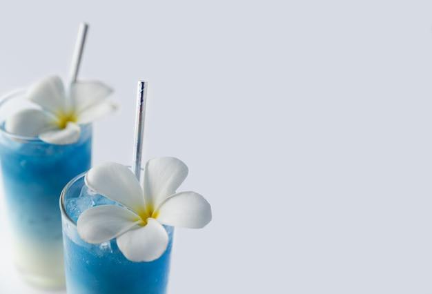 Il latte blu ghiacciato del pisello di farfalla beve con la decorazione tropicale dei fiori. cocktail tradizionali tailandesi sani in vetri Foto Premium