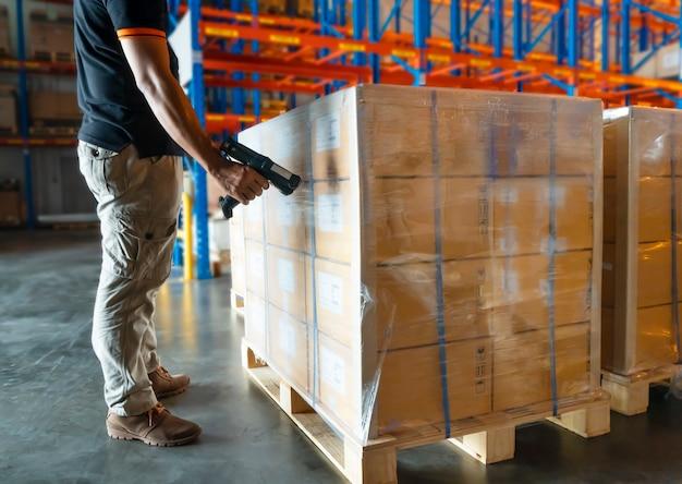 Il lavoratore del magazzino sta analizzando lo scanner di codici a barre con pallet di carico in magazzino. Foto Premium