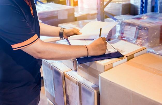 Il lavoratore del magazzino sta lavorando nel deposito del magazzino con l'inventario la spedizione. Foto Premium