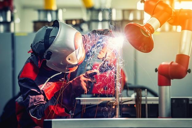 Il lavoratore industriale del saldatore sta saldando la parte di metallo in fabbrica con la maschera protettiva Foto Premium