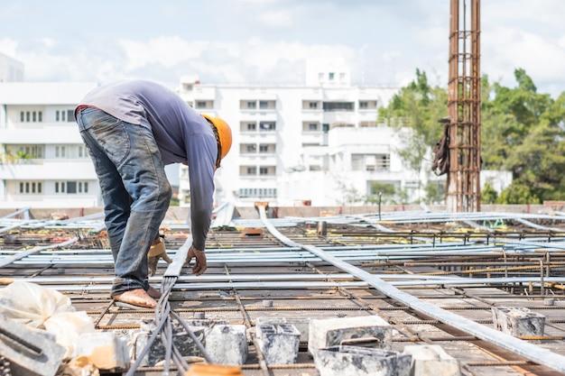 Il lavoratore installa il cavo sul pavimento della costruzione per il sito in costruzione della torre. Foto Premium