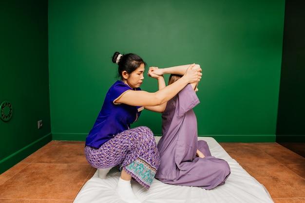 Il lavoratore tailandese del massaggiatore in vestiti asiatici etnici fa le procedure tradizionali della stazione termale alla bella signora bianca in pigiami porpora nella stanza verde di yoga Foto Premium
