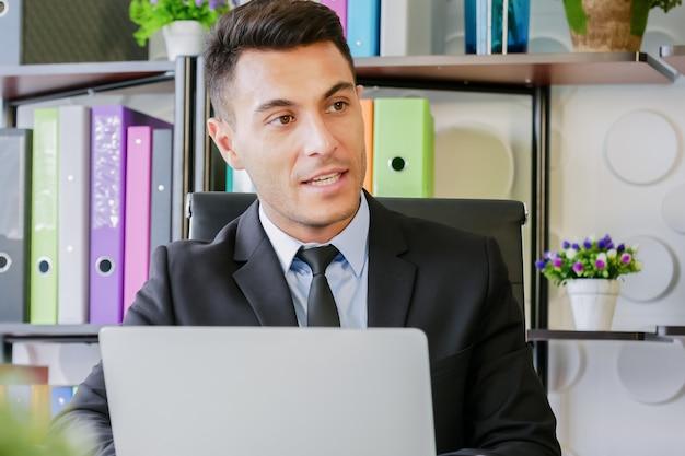 Il lavoro dell'uomo di affari in ufficio moderno usa il computer portatile e sta parlando con qualcuno la gente Foto Premium