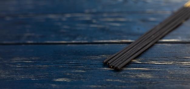 Il legno di sandalo attacca su un tavolo di legno nero. cultura asiatica tradizionale. aromaterapia Foto Premium