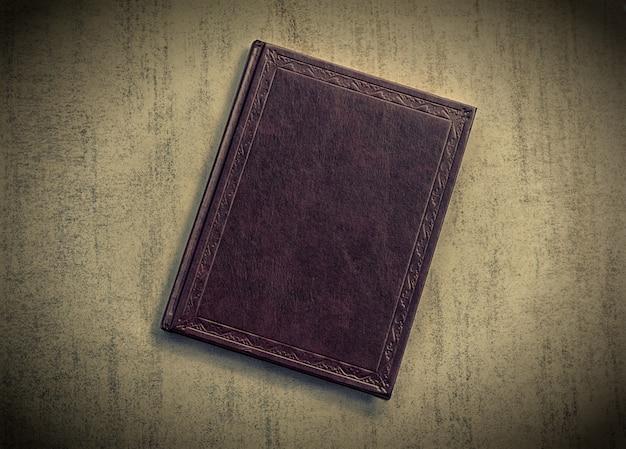 Il libro è viola scuro su uno sfondo grigio grunge, vista dall'alto. foto colorata con vignettatura, retro immagine tonica Foto Premium