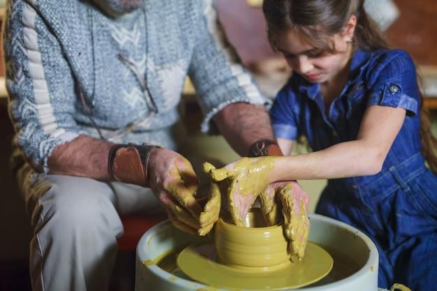Il maestro con il bambino modella una brocca di terracotta. Foto Premium