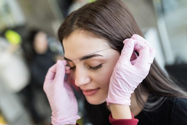 Il maestro controlla il contorno delle sopracciglia modello femminile Foto Gratuite
