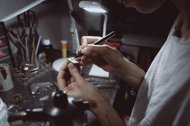 Il maestro elabora il metallo prezioso nell'officina domestica Foto Gratuite
