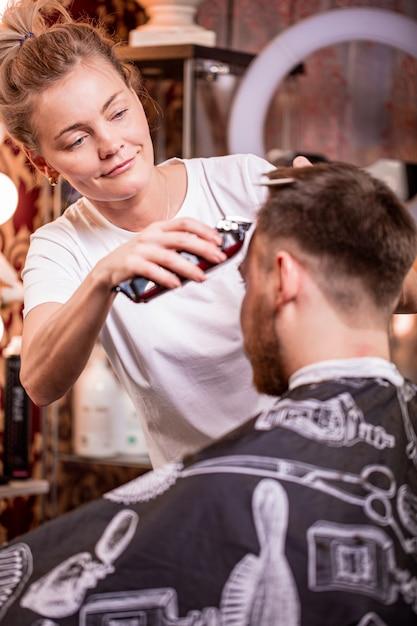 Il maestro taglia i capelli e la barba di un uomo in un barbiere, un parrucchiere fa un taglio di capelli per un giovane. concetto di bellezza, cura di sé. Foto Premium