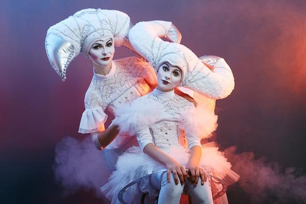 Il mago dell'esecutore circense mostra trucchi con bolle di sapone. una donna e una ragazza gonfiano le bolle di sapone Foto Premium