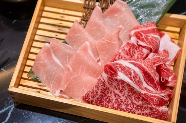 Il maiale e il manzo affettati freschi crudi hanno messo in una scatola quadrata di legno che preparando per shabu Foto Premium