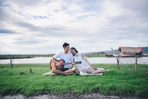 Il marito asiatico che gioca la chitarra e gode di con la sua coppia incinta e il concetto nucleo familiare asiatici all'aperto della moglie. Foto Premium