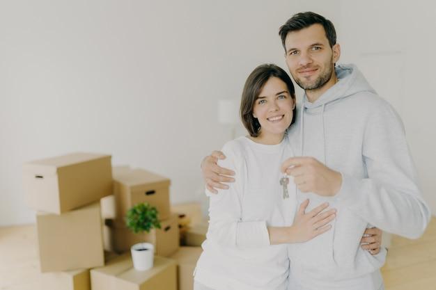 Il marito e la moglie felici acquistano beni immobili, coccolano e tengono le chiavi, stanno in salotto con scatole nella nuova casa Foto Premium