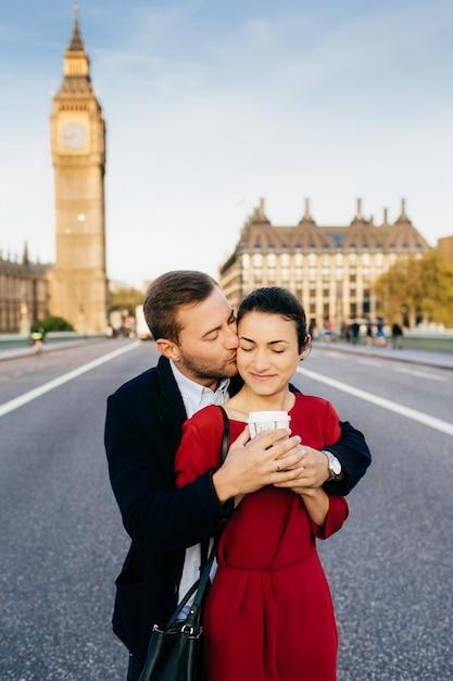 Il maschio e la femmina affettuosi si abbracciano, si baciano, si godono le vacanze a londra, vicino al big ben Foto Premium