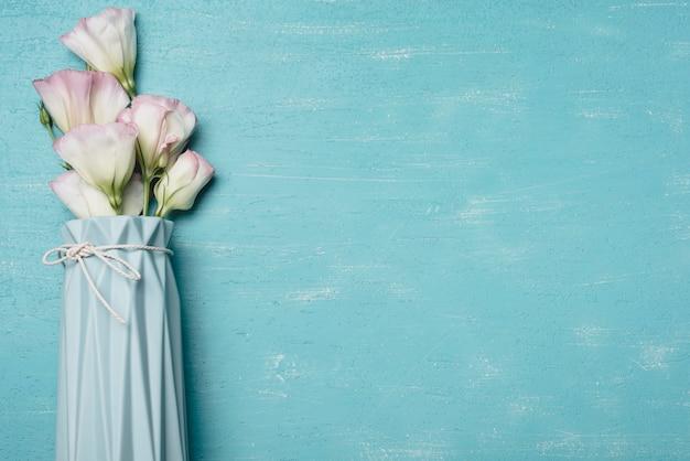 Il mazzo di eustoma fiorisce in vaso sul contesto strutturato blu Foto Gratuite