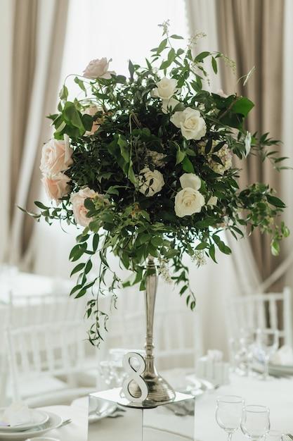 Il mazzo di piante verdi con le rose sta sul tavolo della festa Foto Gratuite