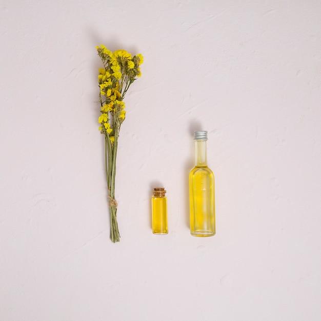 Il mazzo giallo del limonium fiorisce con le bottiglie di olio essenziale sul contesto concreto bianco Foto Gratuite