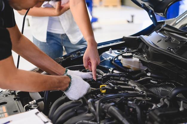 Il meccanico maschio asiatico esamina il problema di ripartizione del motore di automobile davanti a automobilistico Foto Premium